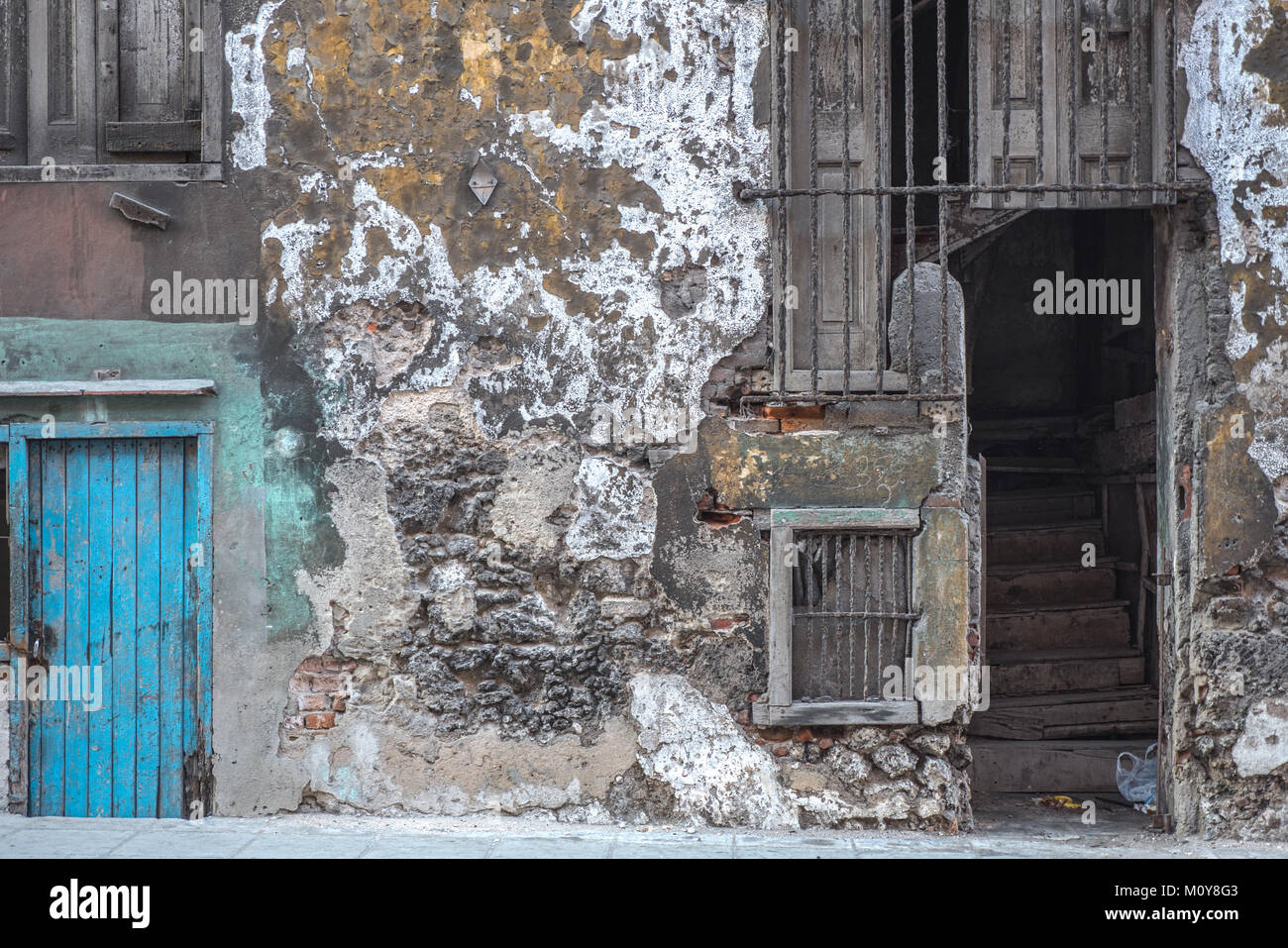 Decrepit colonial building with blue door and staircase in Havana, Cuba - Stock Image