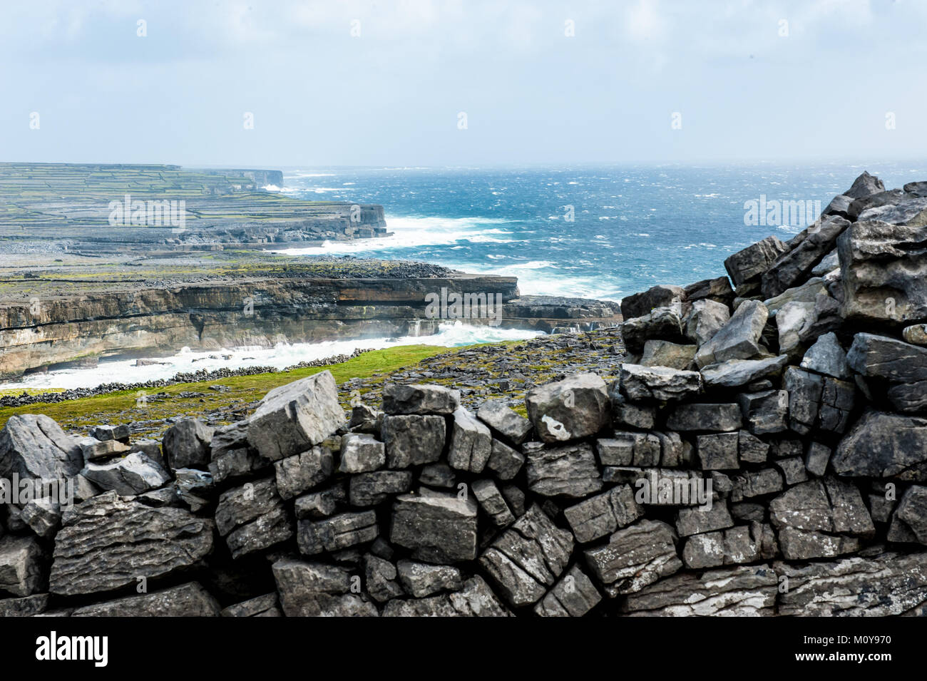 Coastal lanscape with cliffs windy weather and stormy sea on The Aran Islands, a group of three islands located - Stock Image
