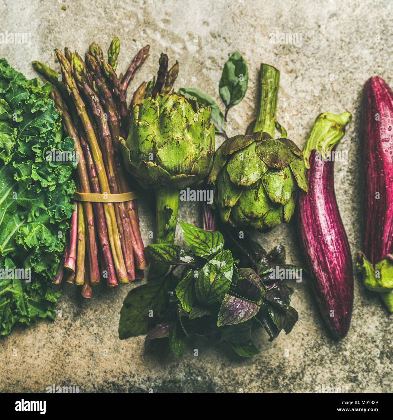Flat-lay of green and purple fresh vegetables over concrete background, top view, square crop. Local produce for - Stock Image