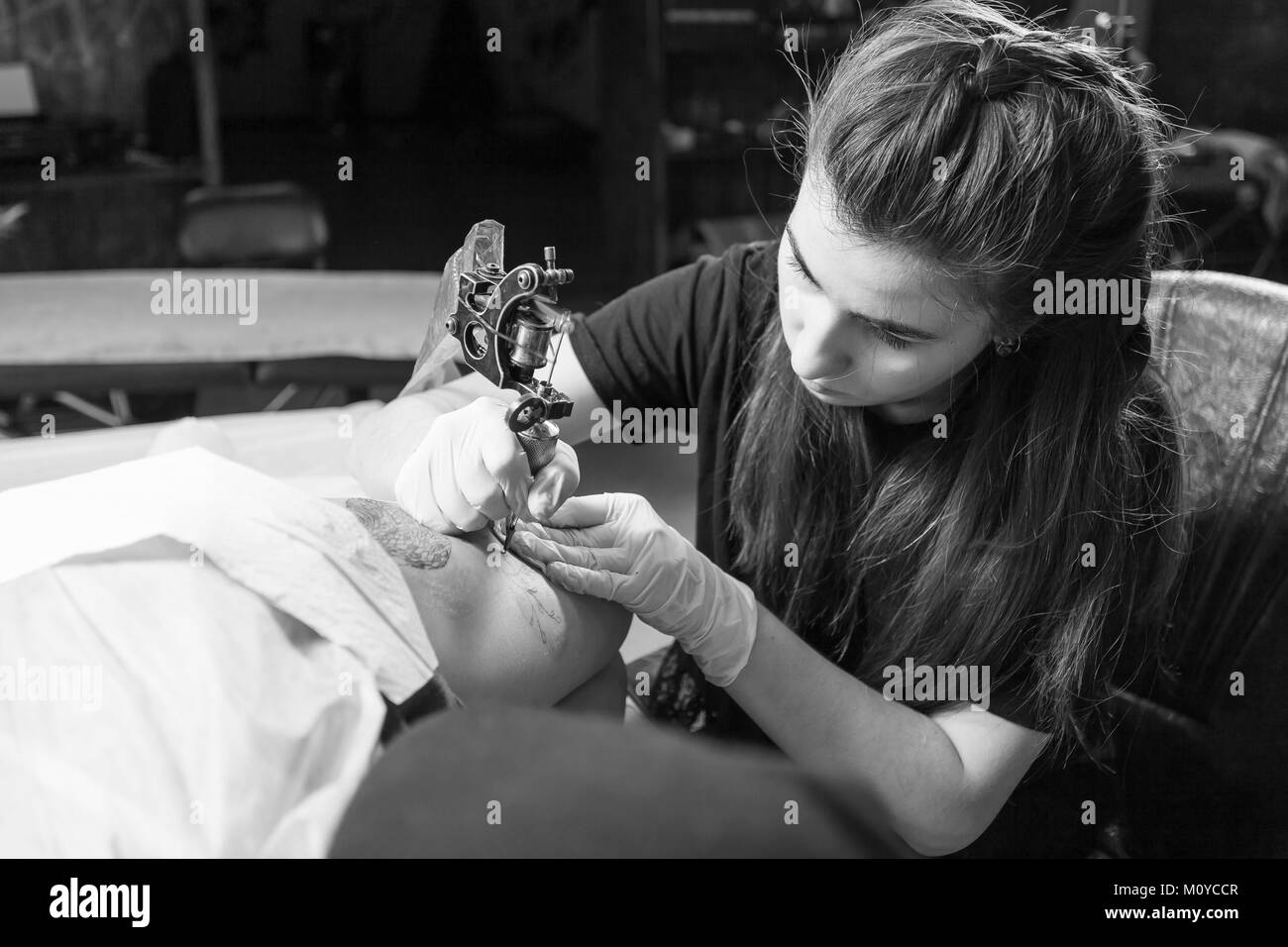 Beautiful dark-haired woman tattoo artist drawing a tattoo for a tattoo, close-up, bottom view - Stock Image