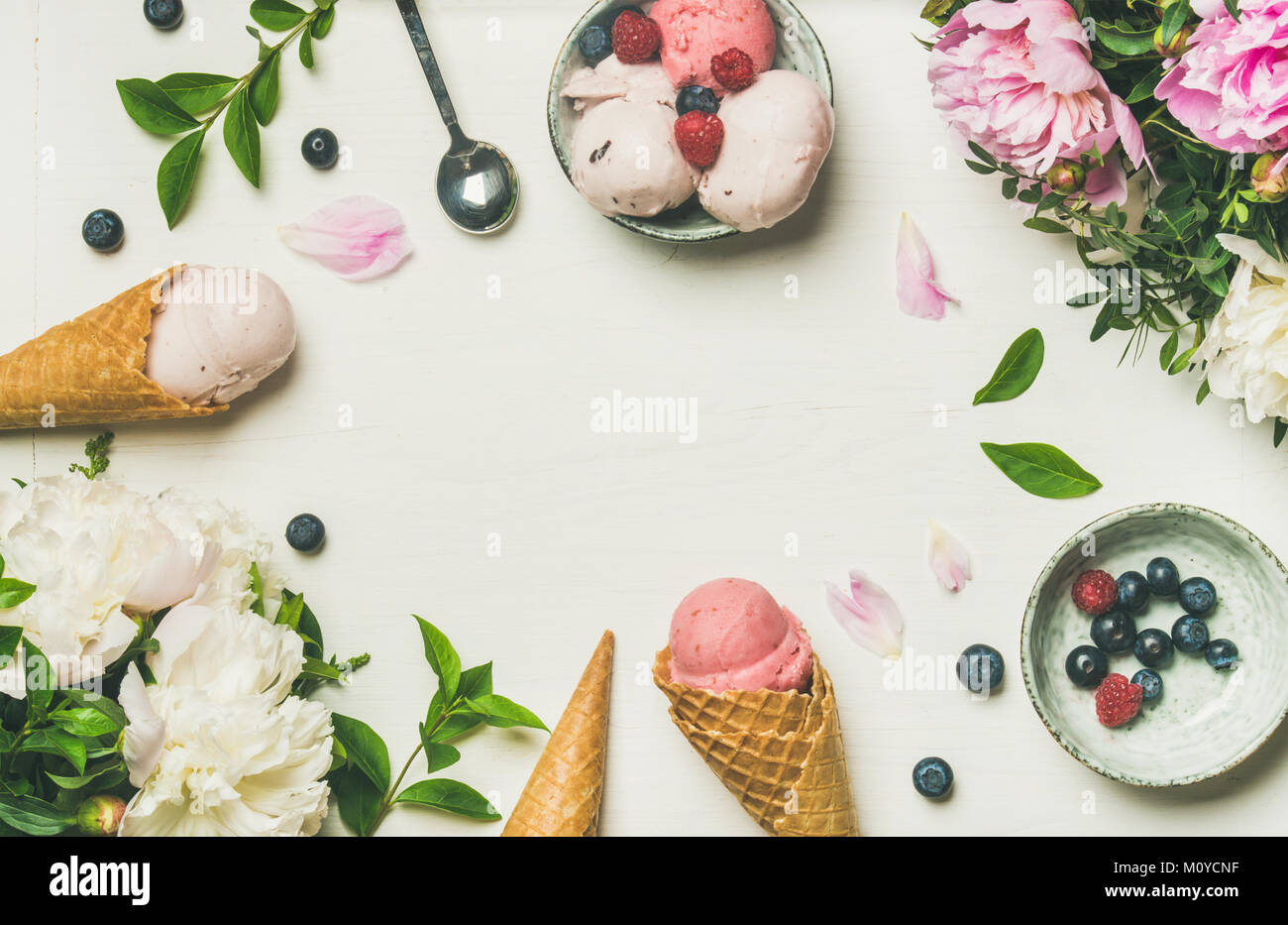 Flatlay of pink strawberry and coconut ice cream scoops, sweet cones and peony flowers bouquet over white background, - Stock Image