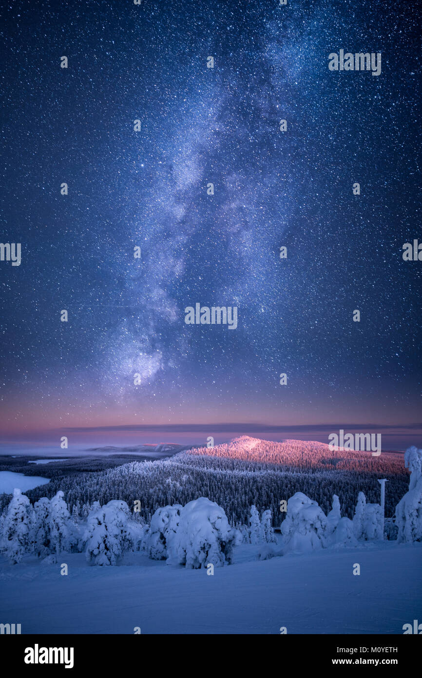 Artistic view of Finnish landscape at winter with milky way glowing on the sky in Ruka, Finland - Stock Image