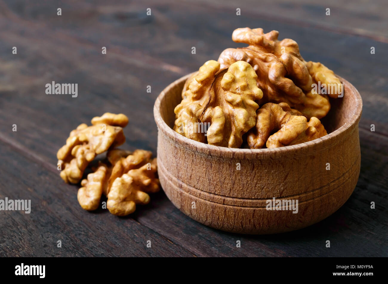 Walnut kernels in a wooden bowl on a dark wooden background. Close-up. - Stock Image