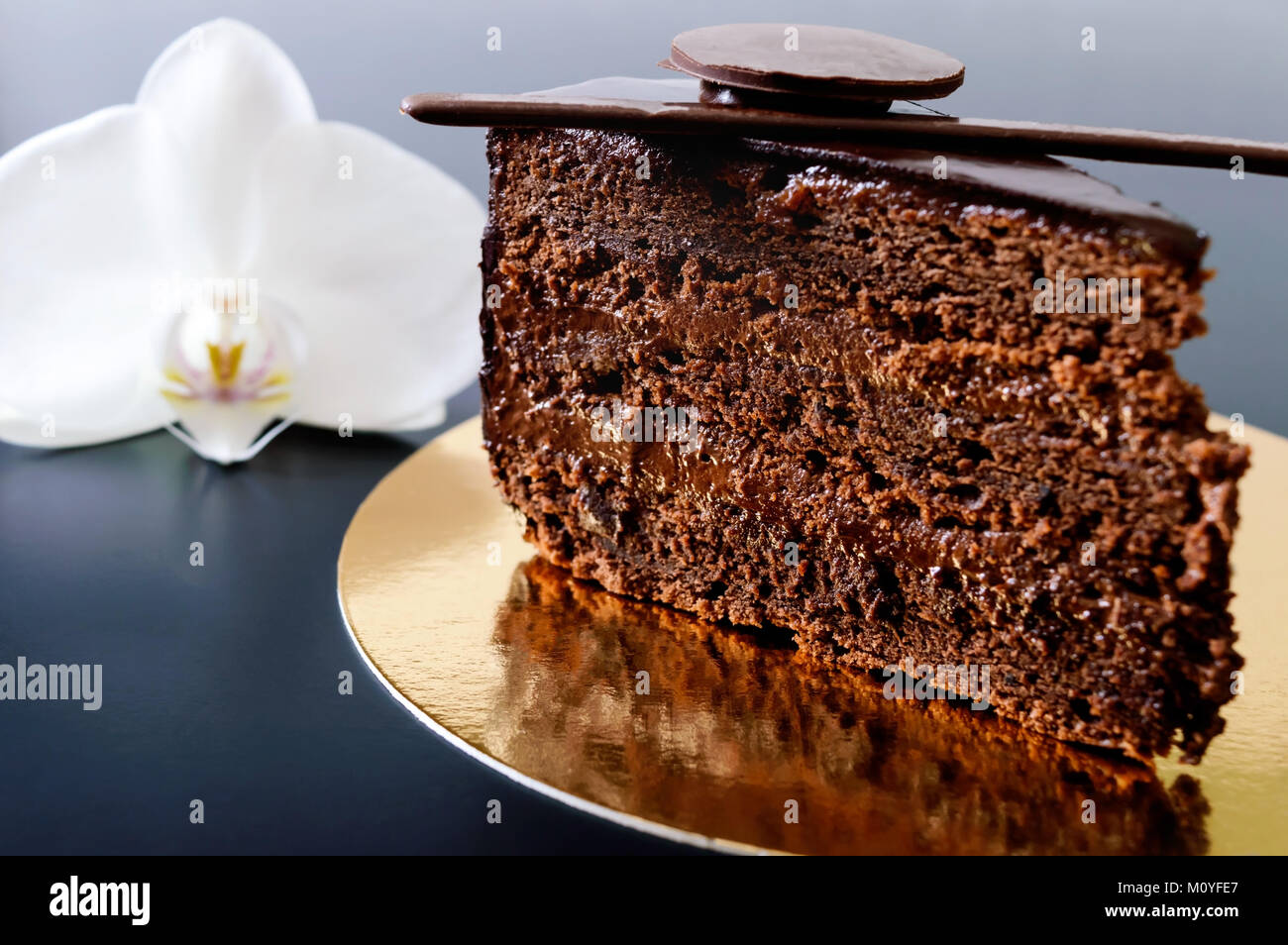 A piece of chocolate cake with chocolate cream on a golden napkin with a white orchid flower on a black background. - Stock Image