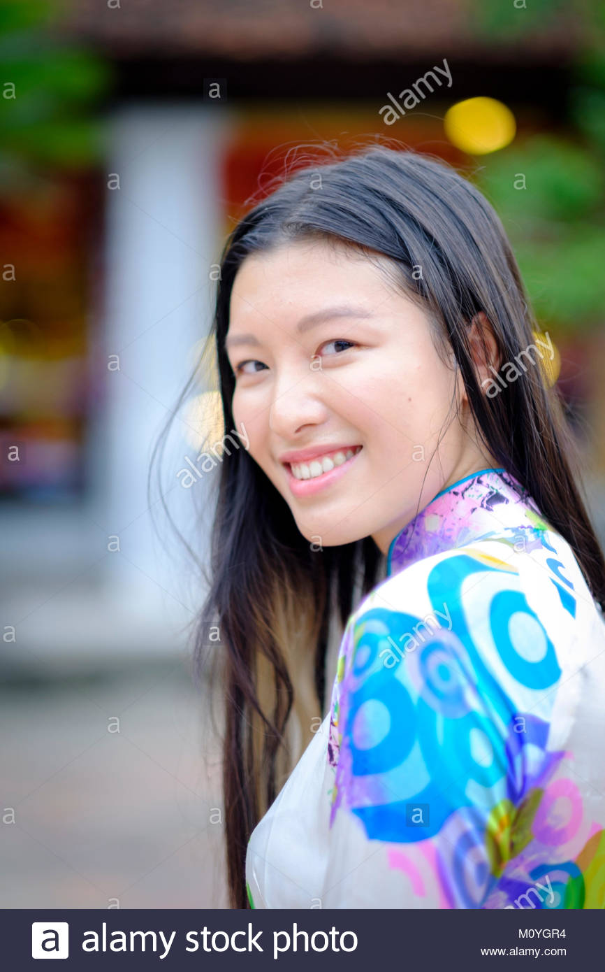 Vietnamese woman smiling and wearing a traditional Ao Dai dress - Stock Image