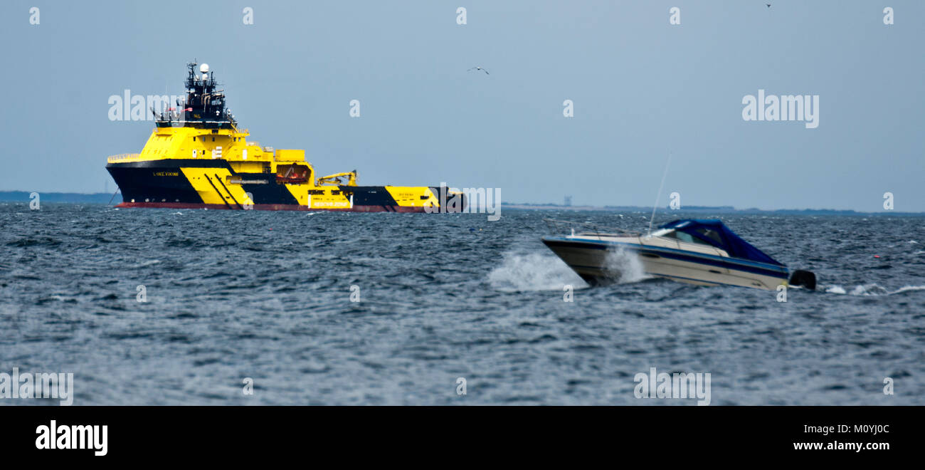 Speedboat passing oil rig supply ship, Nairn - Stock Image