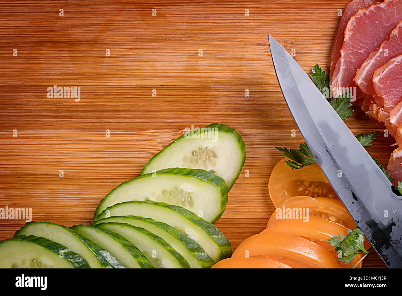 Kitchen knife, ham and vegetables on wet cutting board. Food theme still life with copy space - Stock Image
