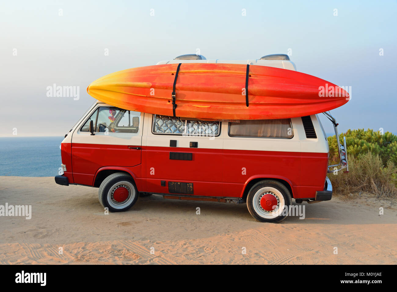 VW bus with kayak at Praia da Marinha,South Coast,Algarve,Portugal - Stock Image