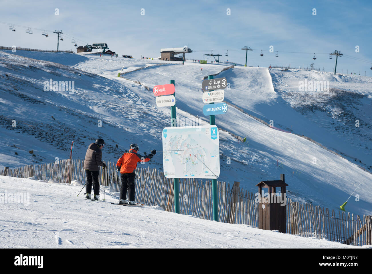 A pair of skiers looking at a piste map above Soldeu, Grandvalaria ski area, Andorra, Europe - Stock Image