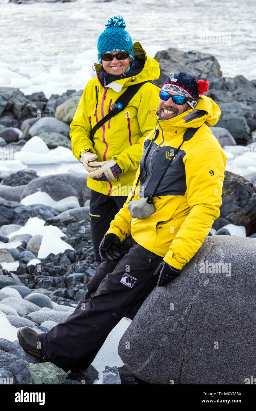 Two professional mountain guides chat on rocky beach; Half Moon Island; Antarctica - Stock Image