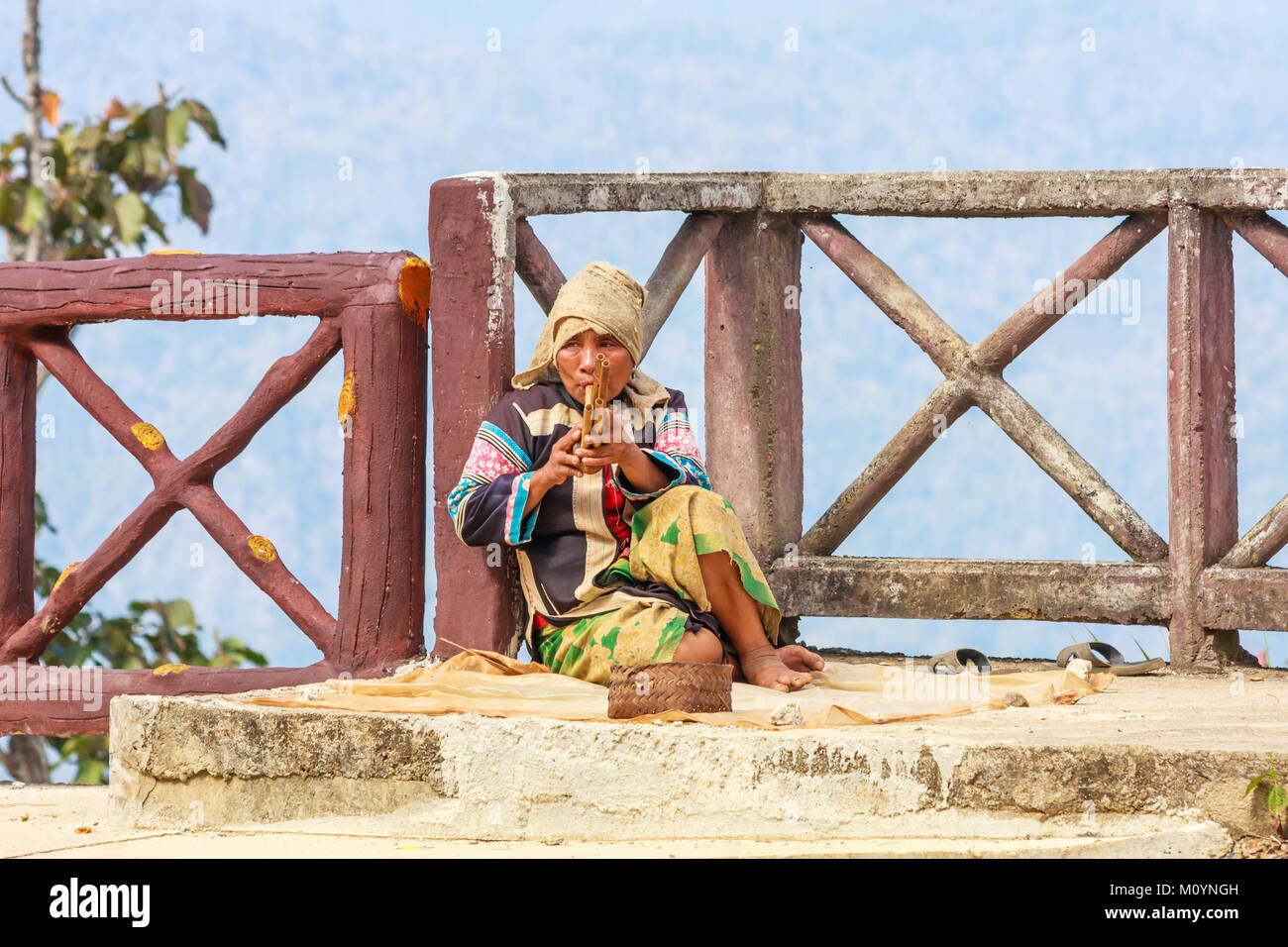 Lahu hilltribe woman playing musical pipes, Tak province, Thailand - Stock Image