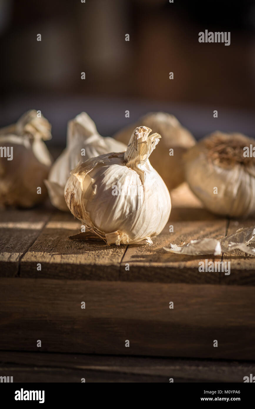 Several heads of fresh garlic on a wooden board with dark background in natural lighting - Stock Image