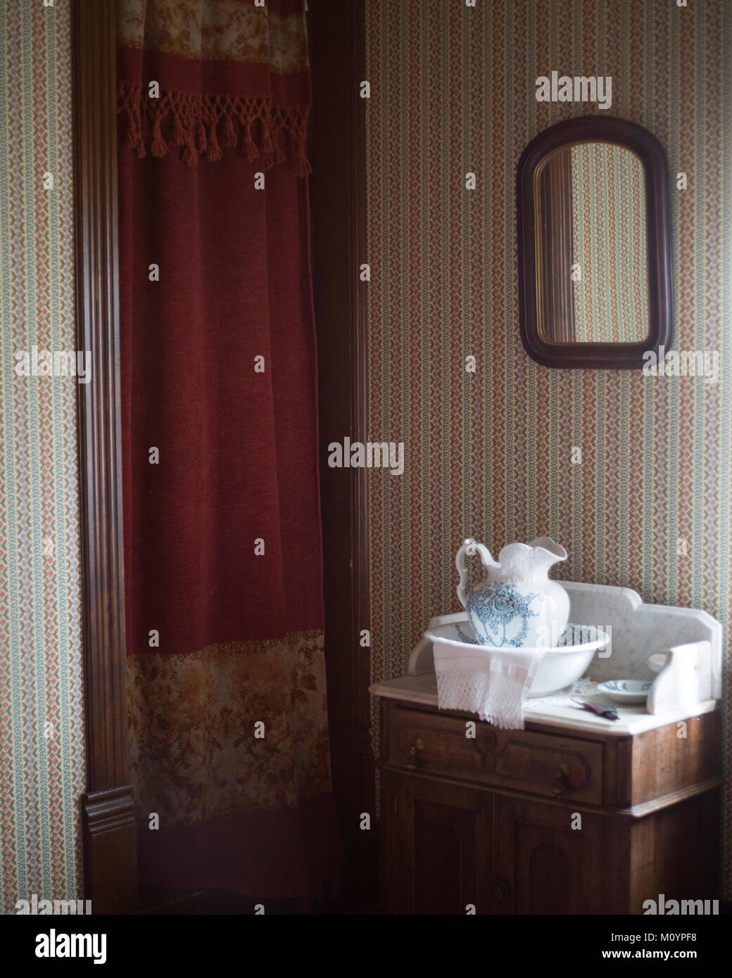 Antique pitcher and wash bowl set in bedroom of 1887 house replica at Heritage Park Historical Village - Stock Image
