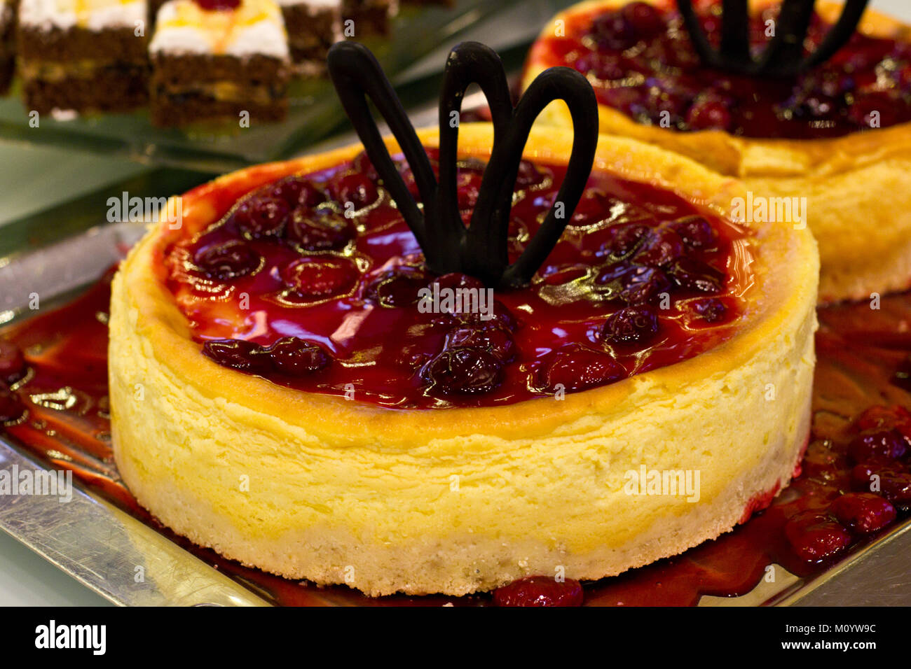 Whole cherry cheesecake with the burgundy jelly and black chocolate - Stock Image