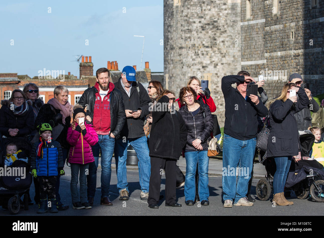 Windsor, UK. 25th January, 2018. Tourists shield their eyes from the sun as they watch the Changing of the Guard Stock Photo