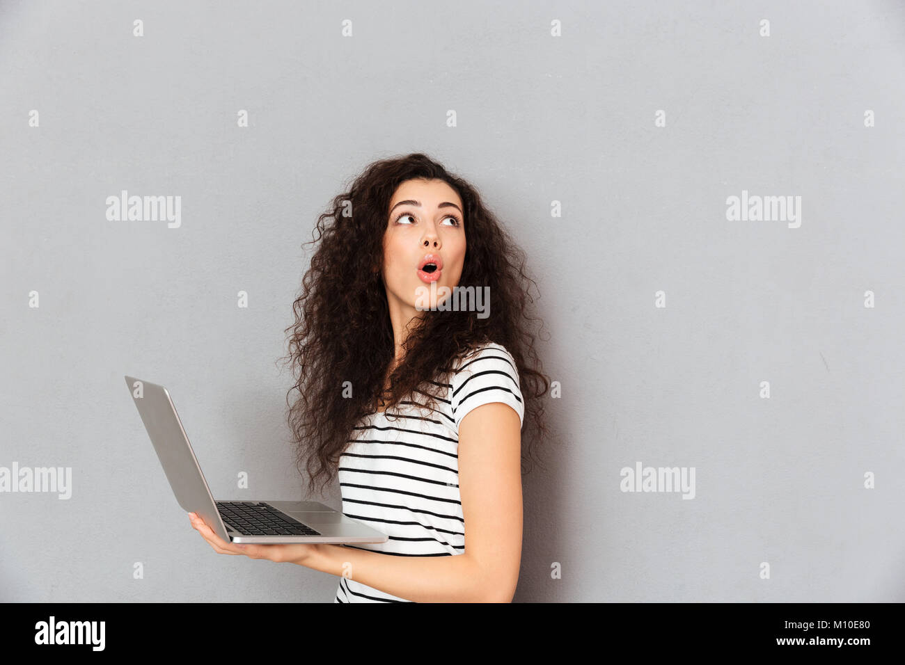 Lovely lady with curly hair posing with silver laptop being isolated over grey background turning around, and paying - Stock Image