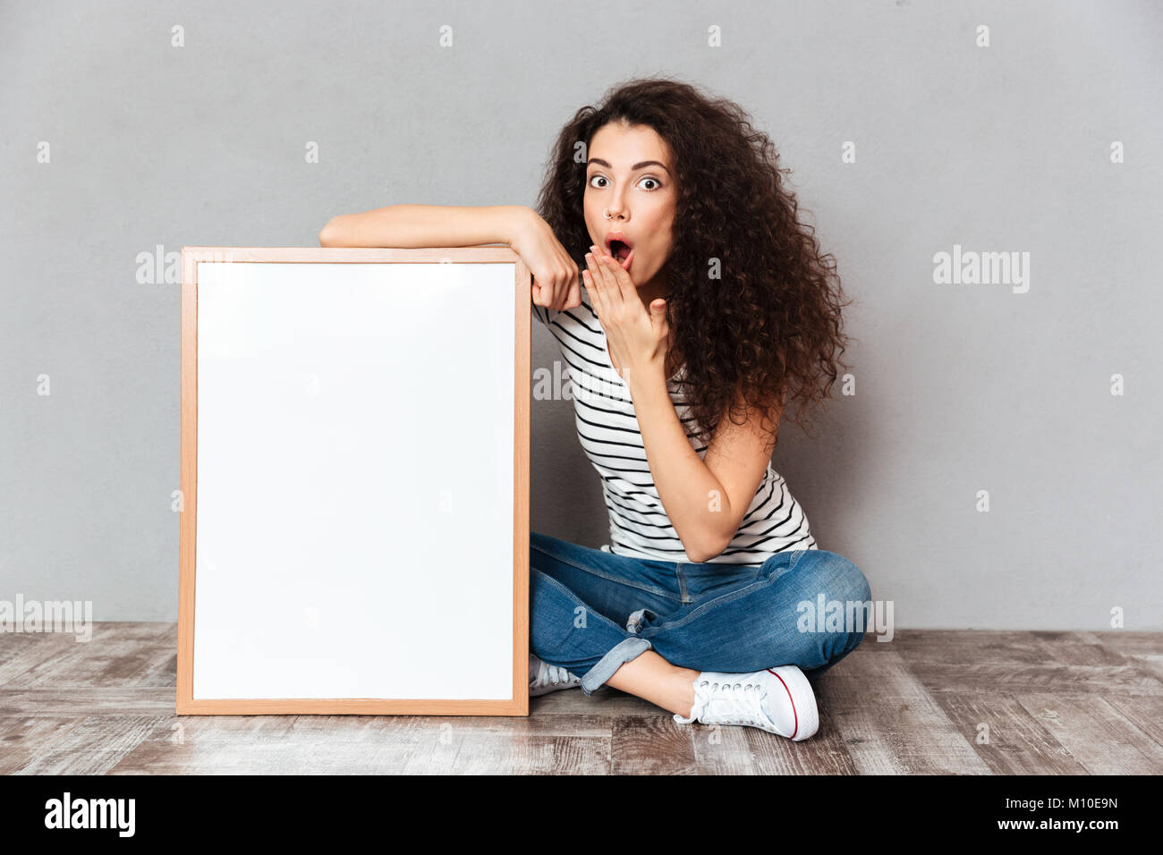 Funny portrait of adult girl in jeans sitting in lotus pose on the floor expressing embarrassment and surprise, - Stock Image