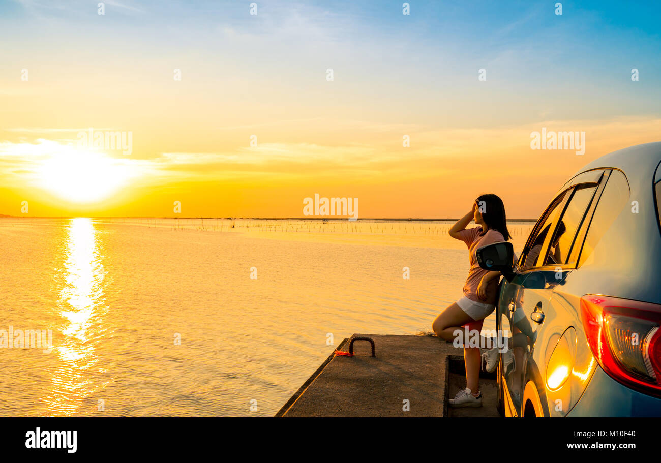 Young Asian woman wear T-shirt, short pants stand leaning blue compact SUV sport car by the sea at sunset with beautiful Stock Photo