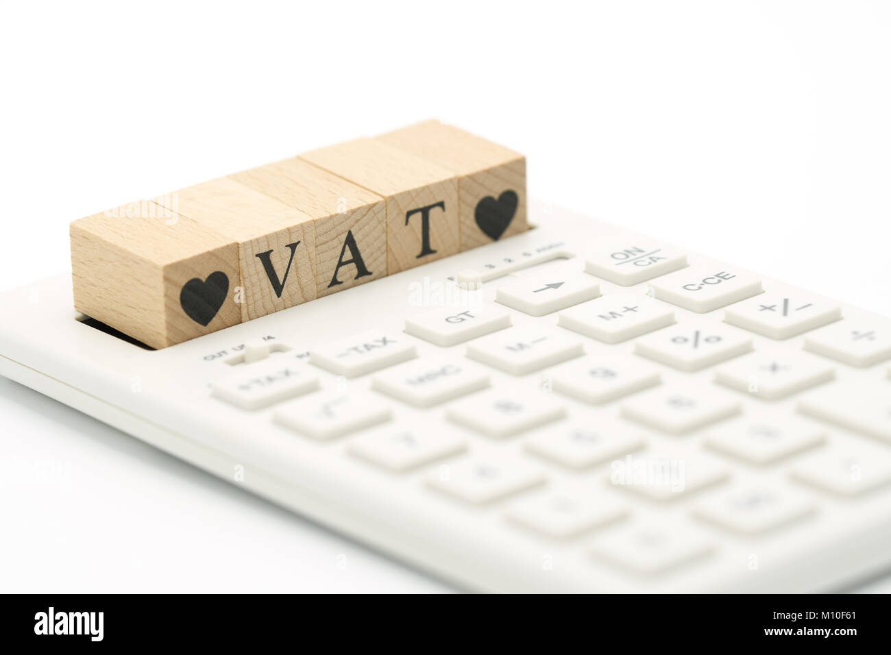 Wood word VAT and Wood Heart placed on a white calculator as background finance concept and business concept with - Stock Image