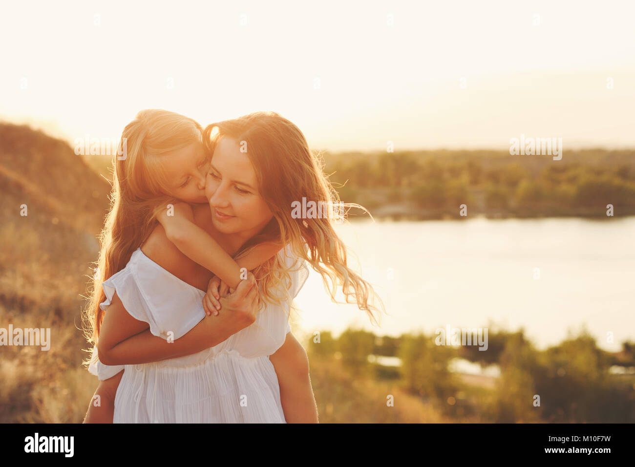 Mother Piggyback the daughter. Little girl is happy and kisses mother on cheek. Family fun in the countryside. In - Stock Image