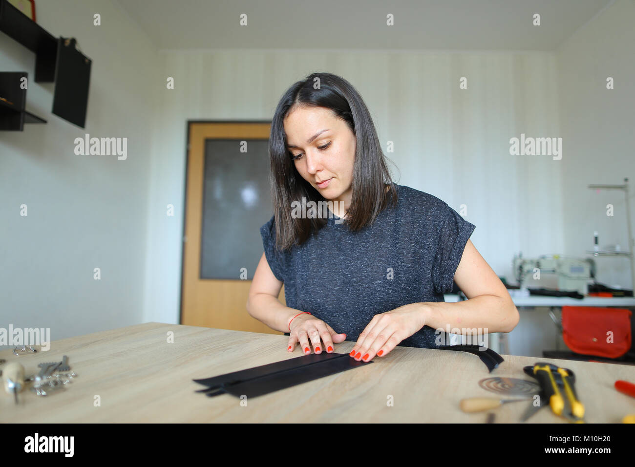 girl preparing leather for making purse. - Stock Image
