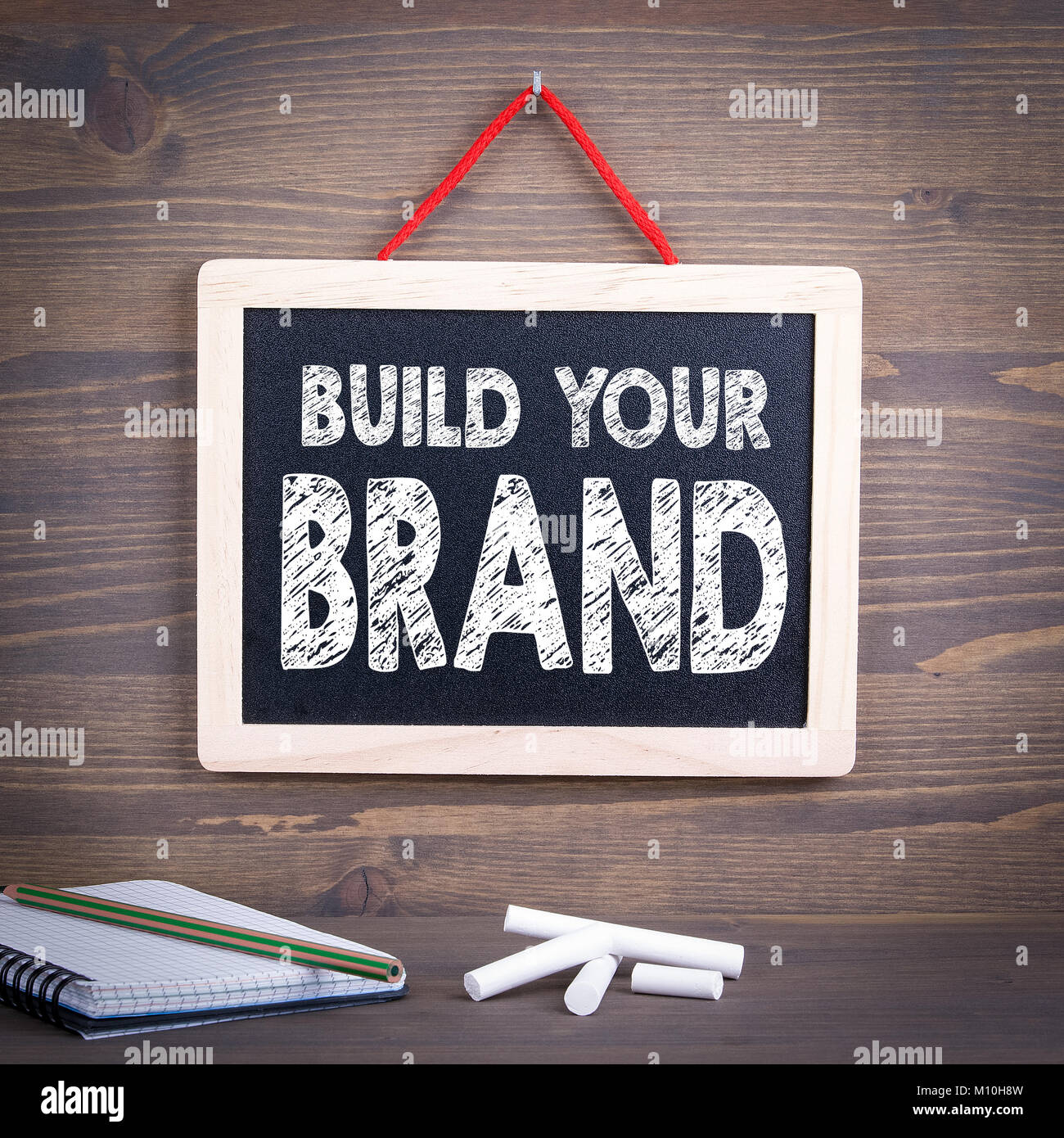 build your brand concept. Chalkboard on a wooden background - Stock Image