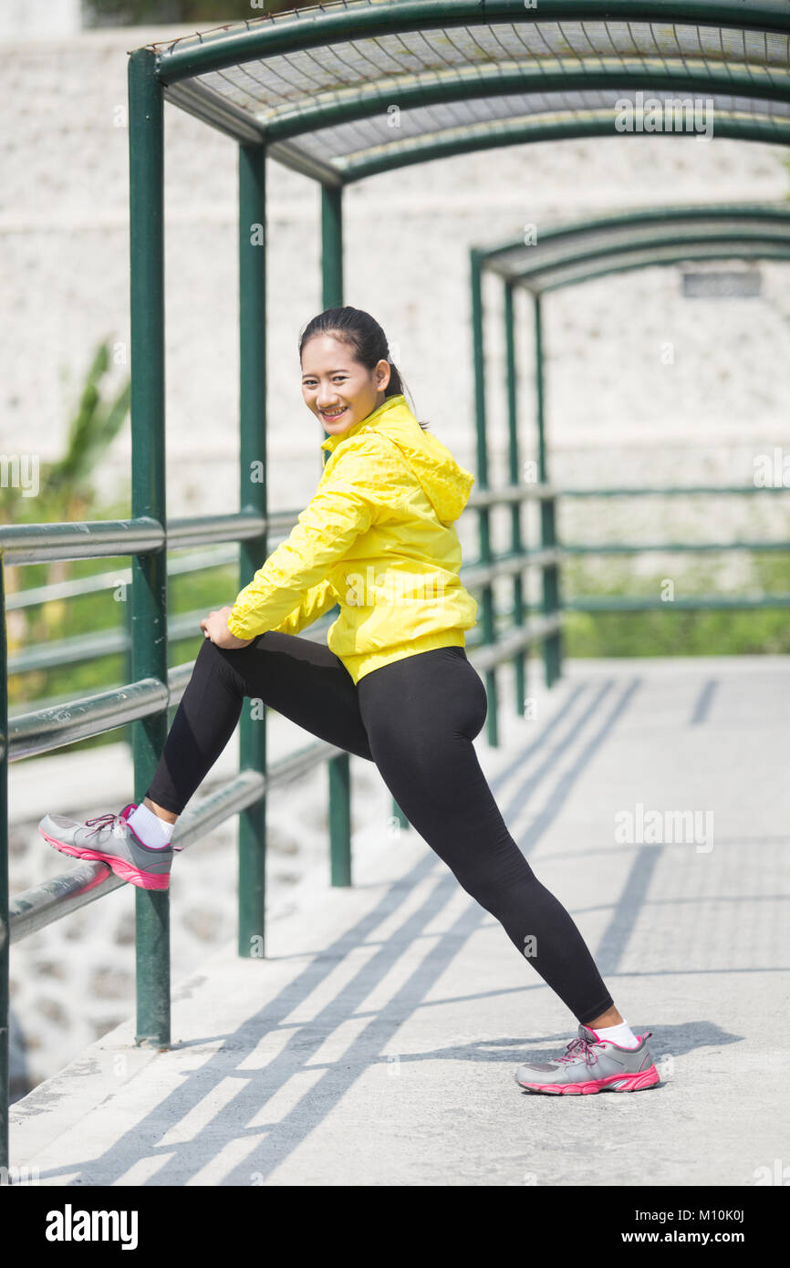 A portrait of a young asian woman stretching outdoor in yellow neon jacket Stock Photo