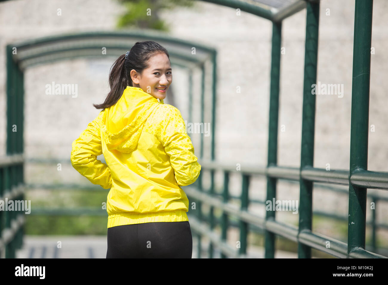 A portrait of a young asian woman exercising outdoor in yellow neon jacket Stock Photo