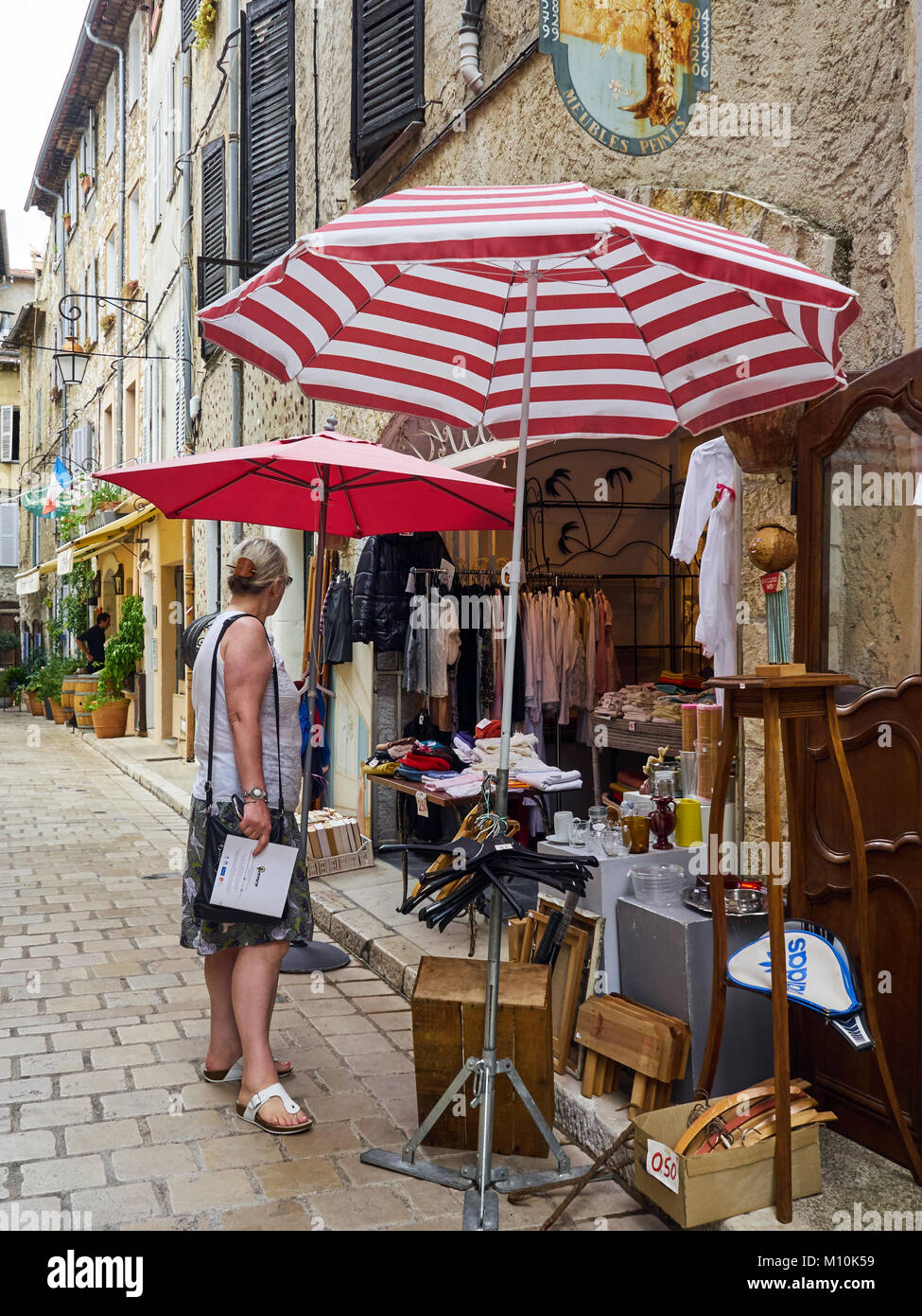 Street in the old town, Vence, South of France, with shopper looking at items in secondhand shop - Stock Image