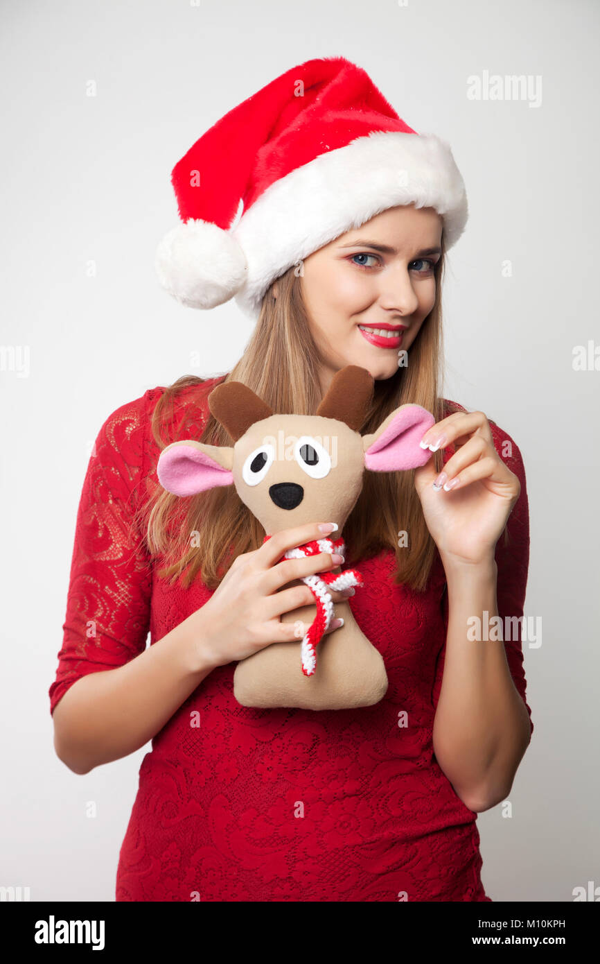Woman in Santa Hat holding reindeer toy - Stock Image