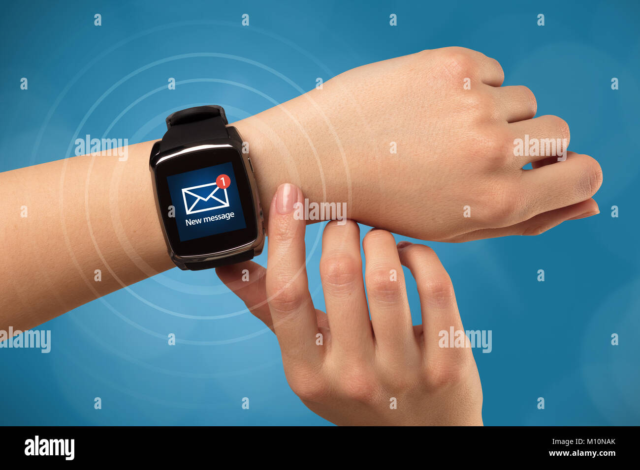 Female hand receives new message on her smartwatch - Stock Image