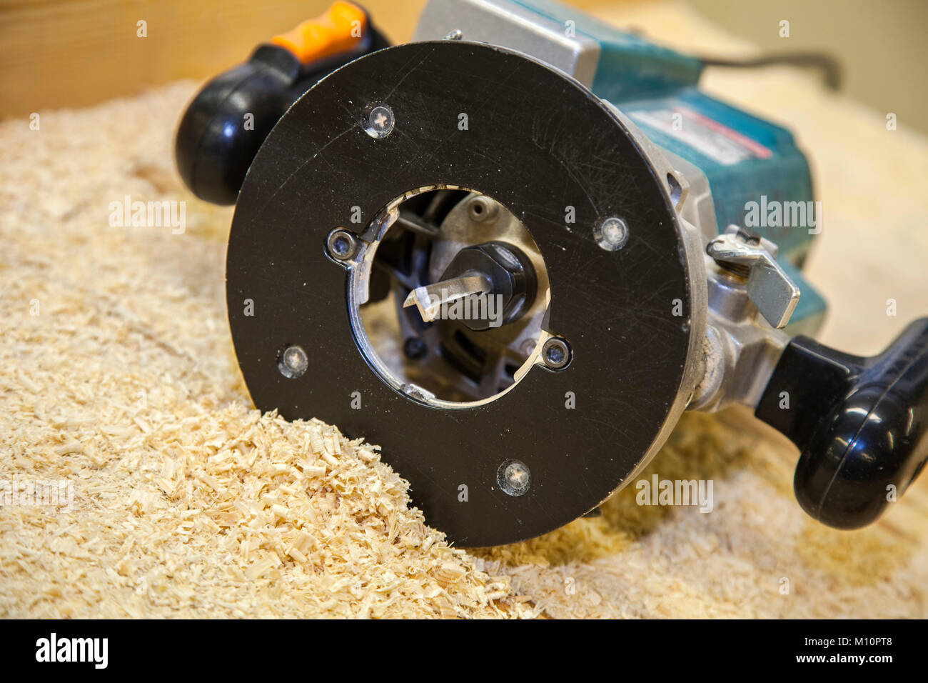 View of a router on a work bench with wood shavings. - Stock Image