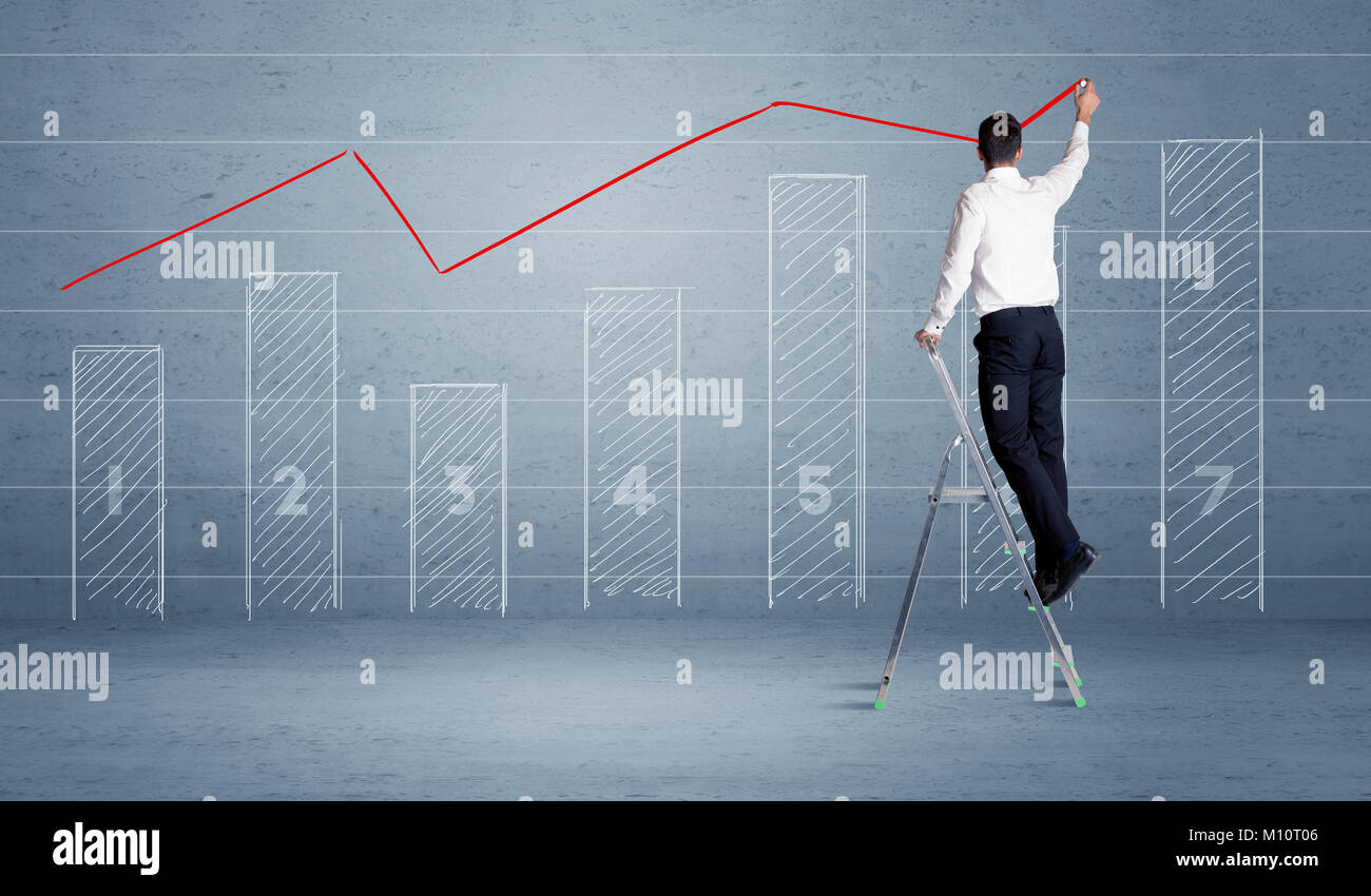 A man in elegant suit standing on a small ladder and drawing a chart on blue wall background with numbers, lines, - Stock Image