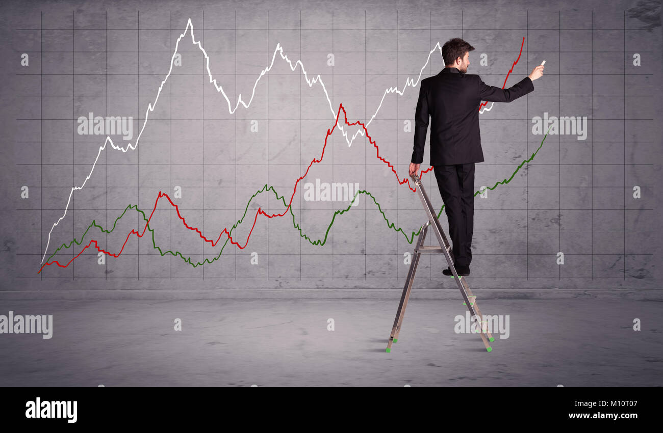 A guy in modern suit standing on a small ladder and drawing a chart on grey wall background with exponential progressing - Stock Image