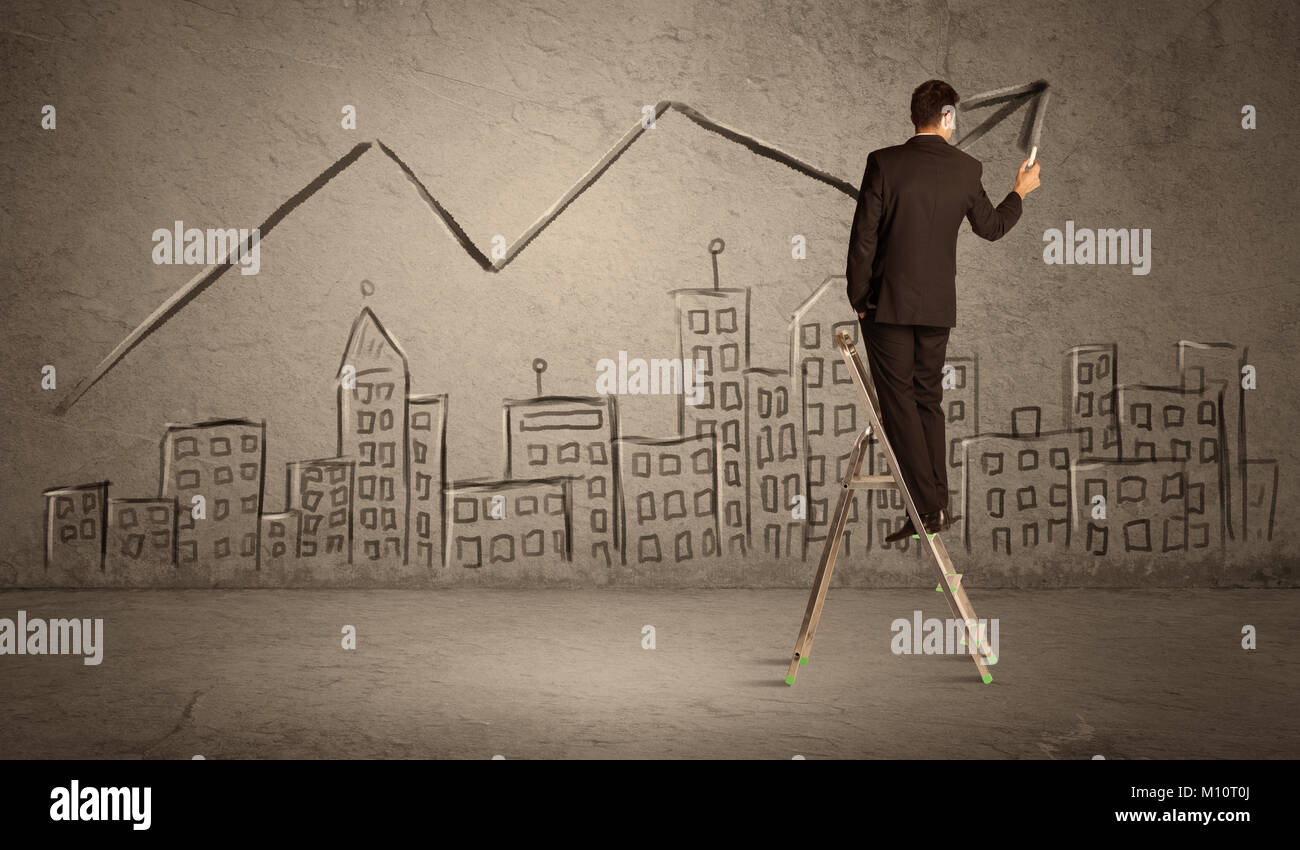 A man in elegant suit standing on a small ladder and drawing a line on brown wall background with buildings - Stock Image