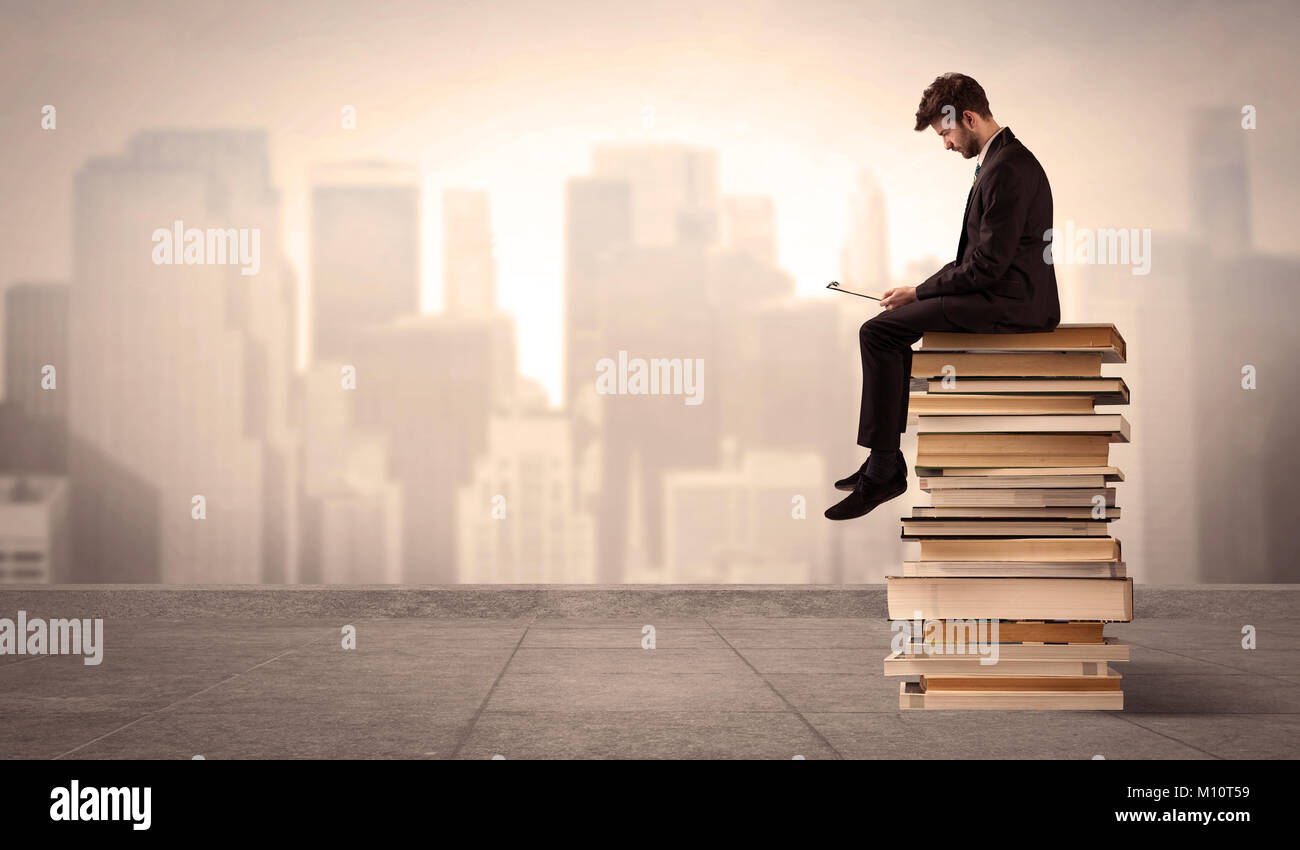 A serious businessman with laptop tablet in elegant suit sitting on a stack of books in front of cityscape - Stock Image