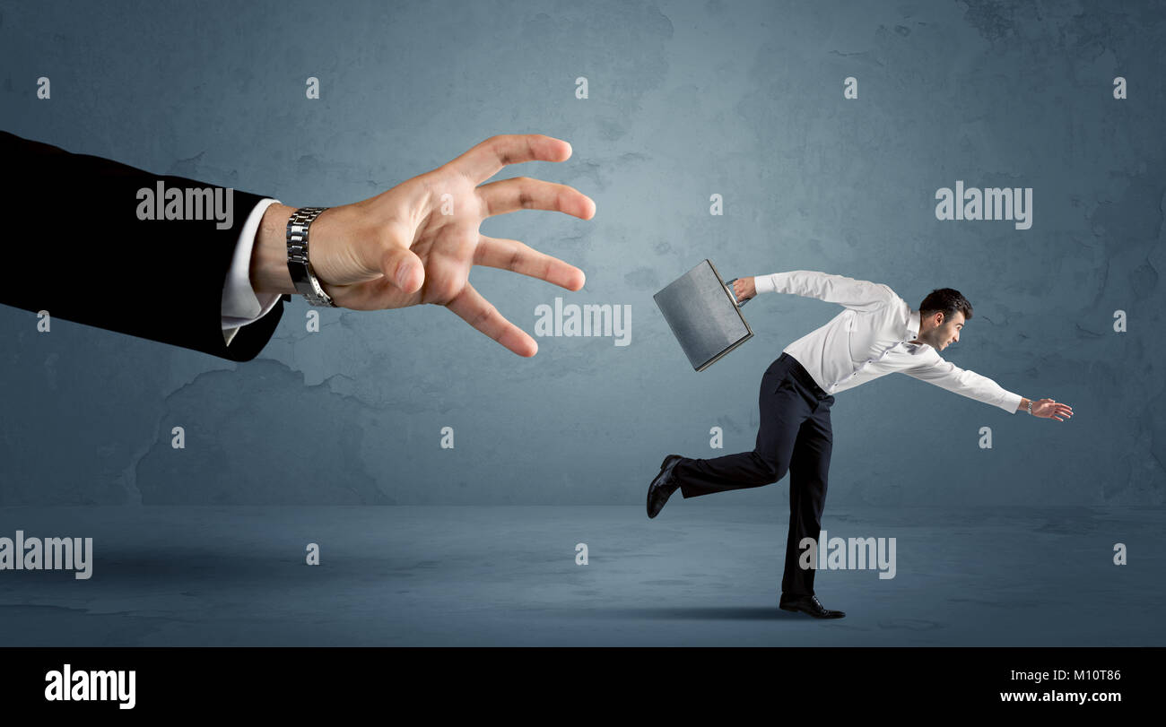 Business man running away from a huge hand concept on background - Stock Image