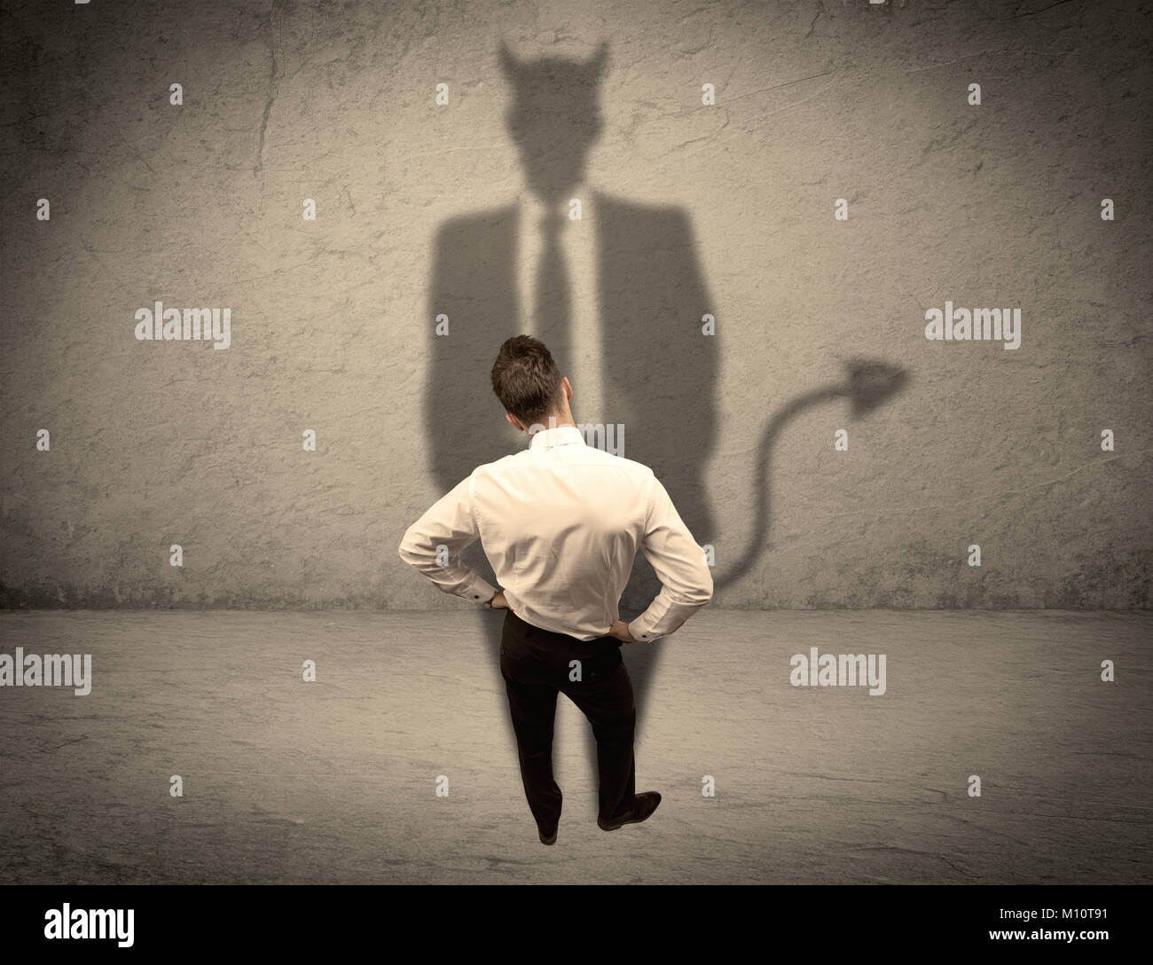 An experienced tricky businessman in suit looking at his devil desguise shadow reflected on the wall concept - Stock Image