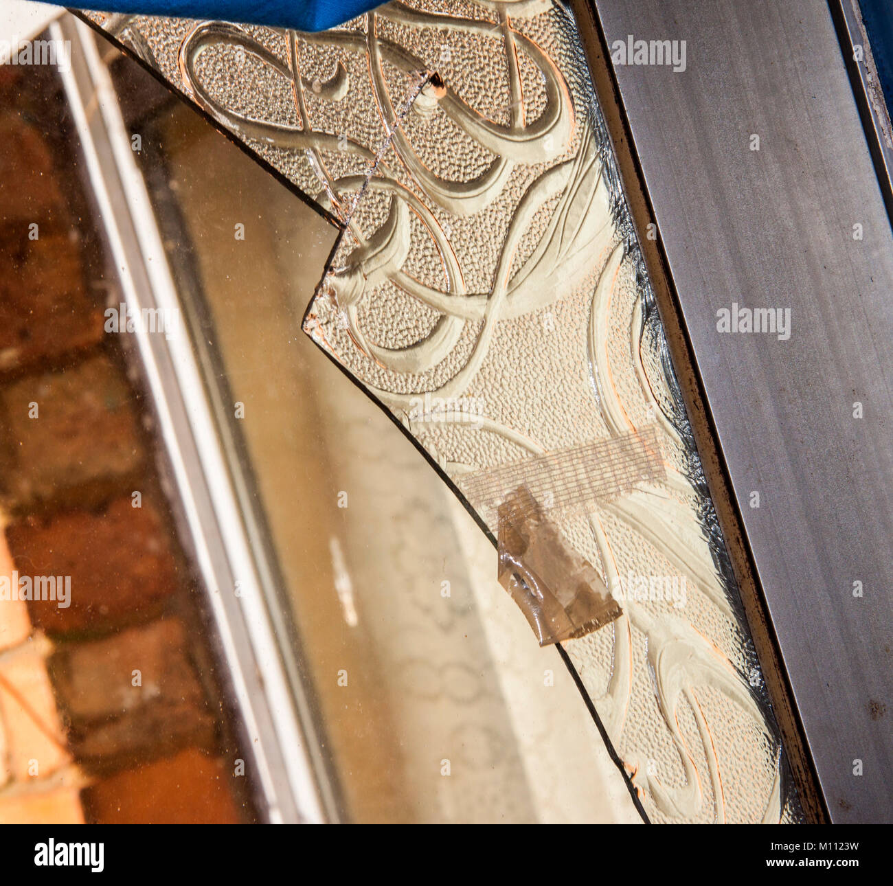 Shard of broken obscure glass in a damaged window frame. - Stock Image
