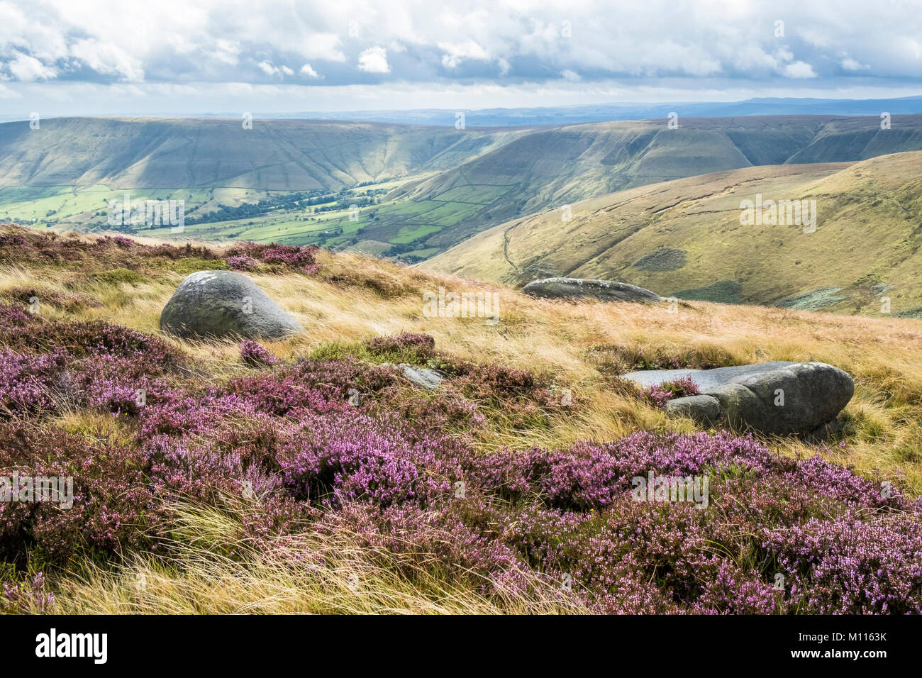 View from Kinder Scout towards Dalehead in the Vale of Edale with sunshine breaking through cloud onto moorland - Stock Image