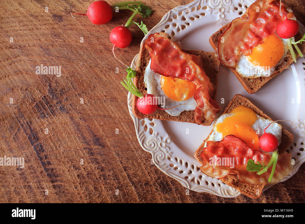 Breakfast , crispy bacon, fried eggs and bread. Sandwiches on white plate. Rustic table . Top view - Stock Image