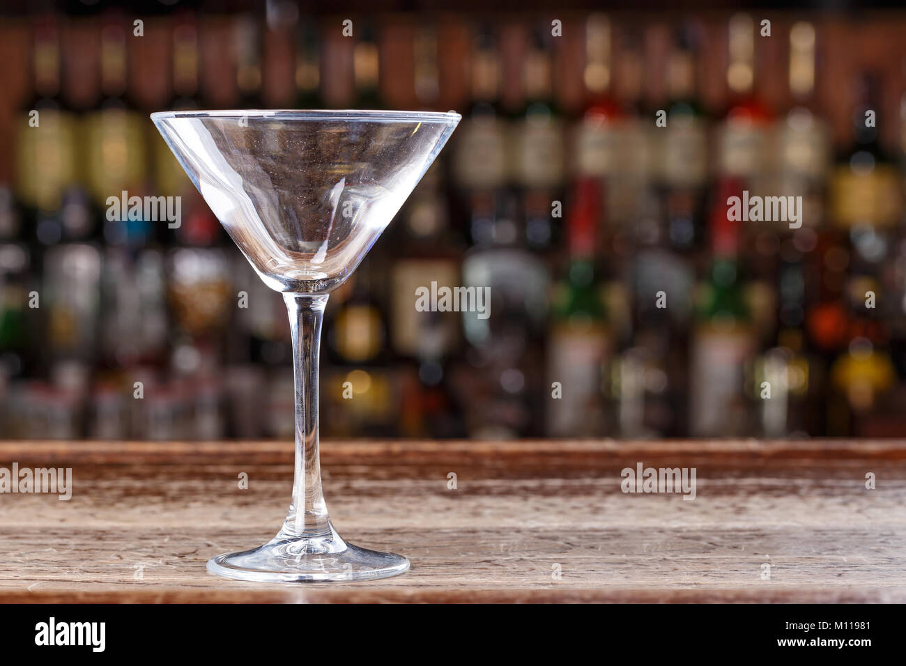 An empty martini glass stands on the bar in the restaurant, on a blurry background of alcohol - Stock Image