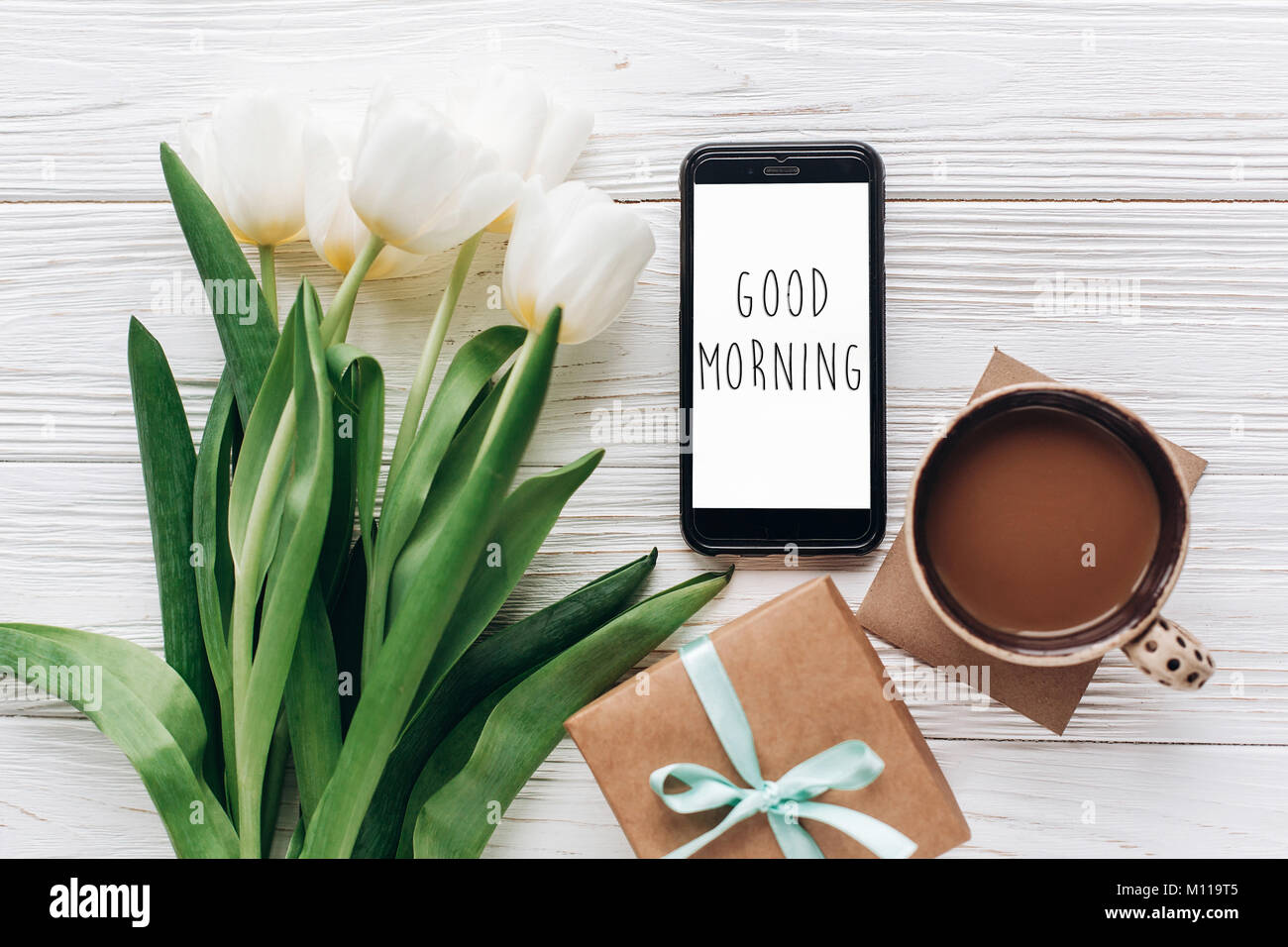 Good morning text sign on phone screen and stylish gift and tulips good morning text sign on phone screen and stylish gift and tulips and coffee on white wooden rustic background flat lay with flowers and gadget wit negle Gallery
