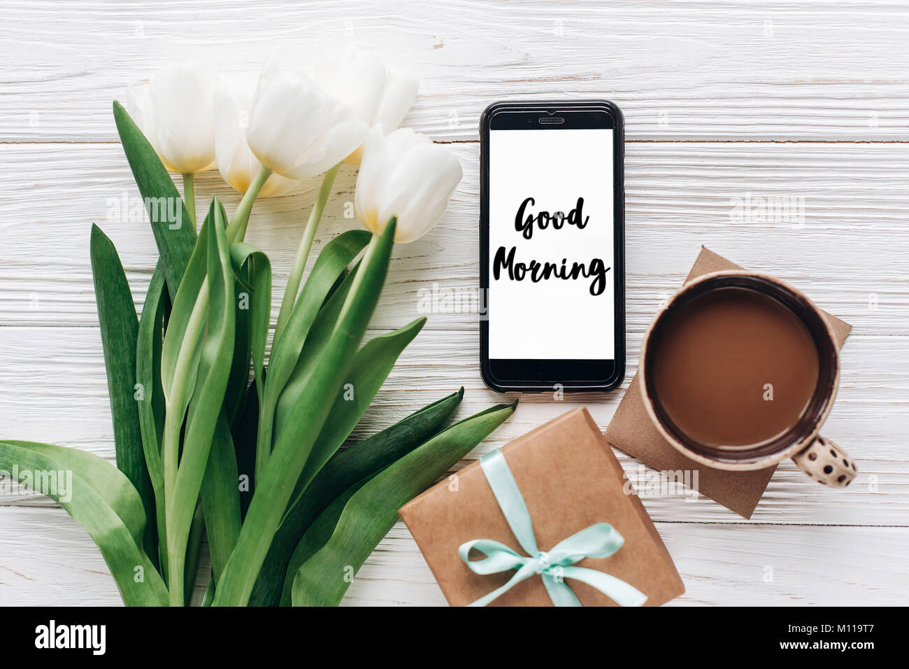 Good morning text sign on phone screen and stylish gift and tulips good morning text sign on phone screen and stylish gift and tulips and coffee on white wooden rustic background flat lay with flowers and gadget spa negle Choice Image