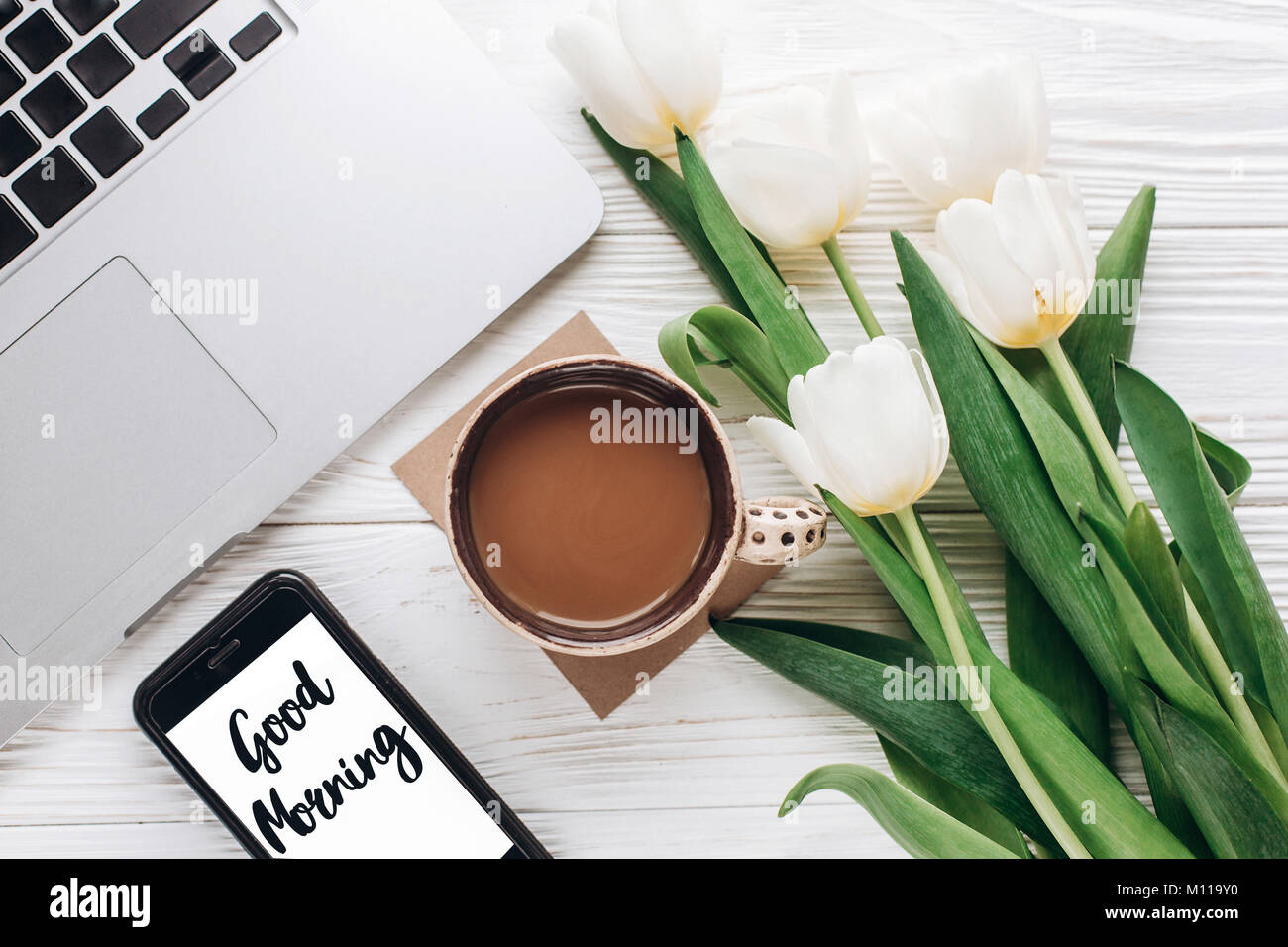 good morning text sign on phone screen and laptop with morning coffee and tulips on white wooden rustic background. - Stock Image