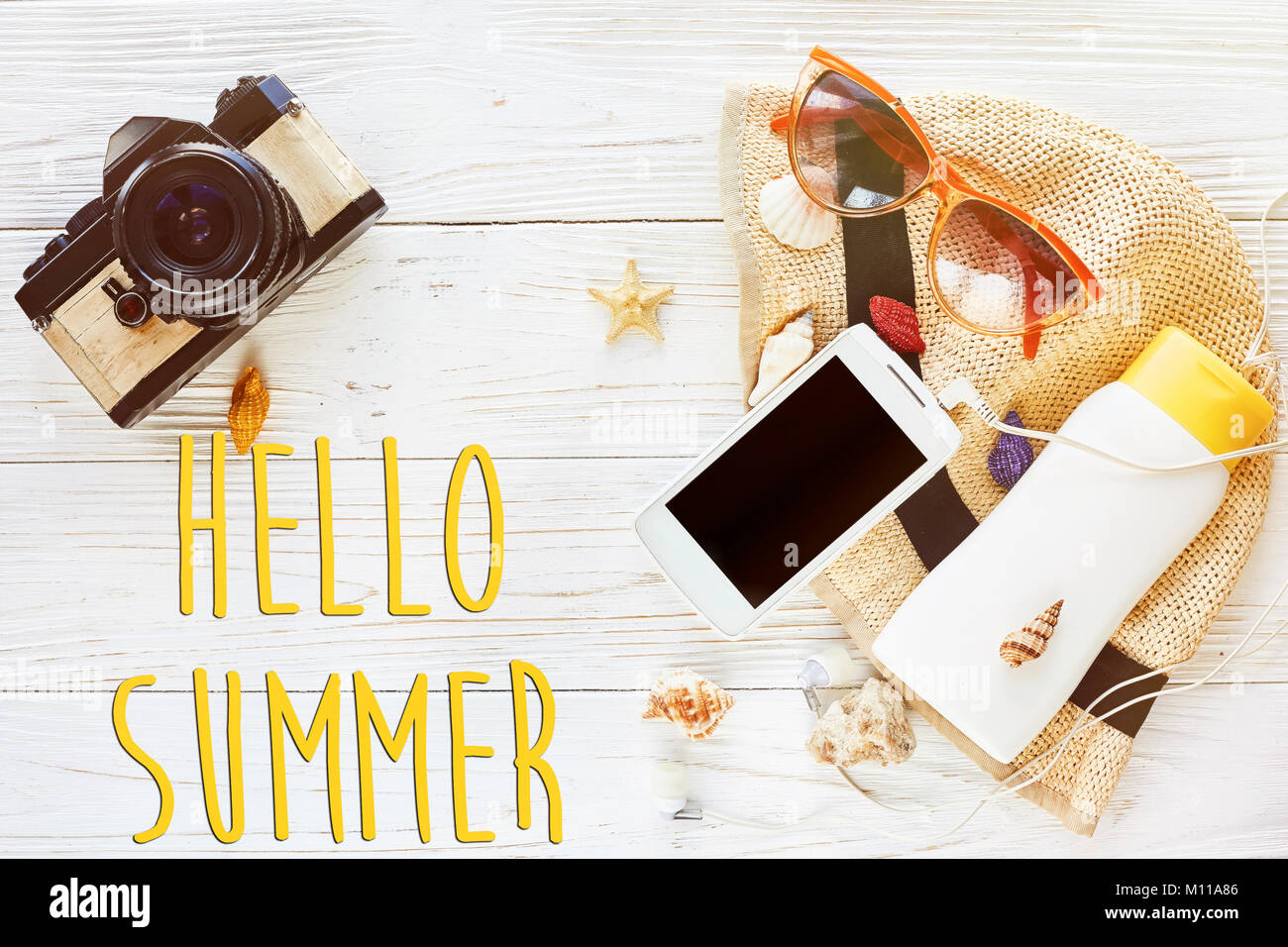 hello summer text, travel vacation flat lay concept. photo camera and hat sunscreen phone with empty screen and sunglasses on white wooden background, Stock Photo