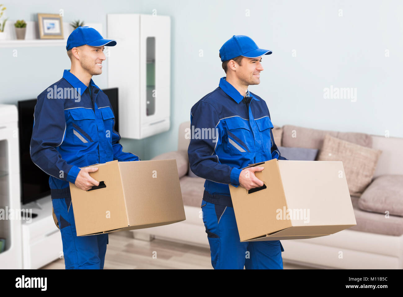 Young Smiling Professional Movers In Uniform Delivering Cardboard Boxes In Living Room Stock Photo