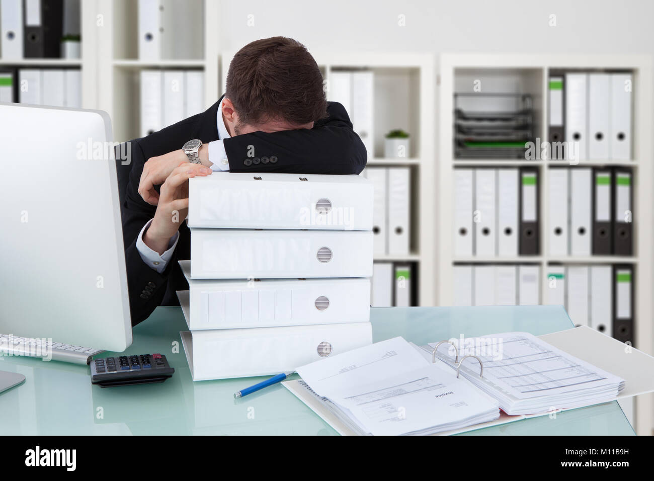 Businessman Sleeping On Stack Of Folders In Office - Stock Image