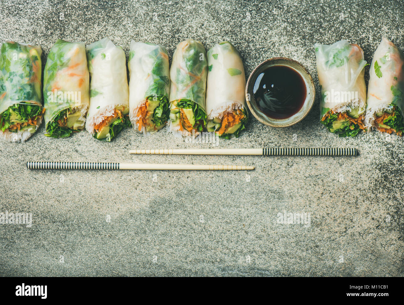 Helathy Asian cuisine. Flat-lay of vegan spring or summer rice paper rolls with vegetables, sauce and chopsticks - Stock Image