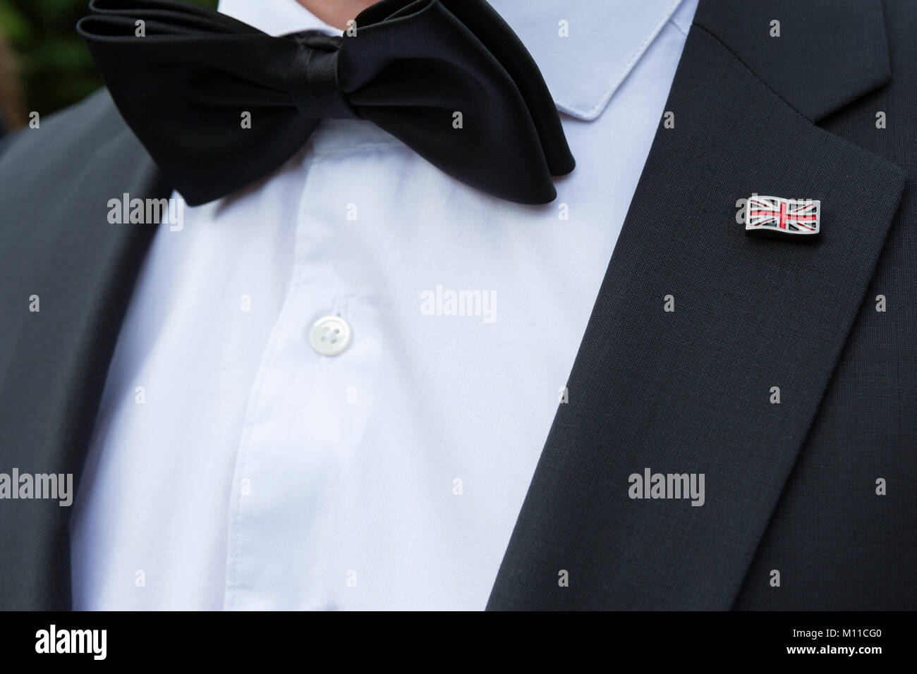 Man in formal dinner dress with black bow tie and British Union Jack flag lapel badge - Stock Image